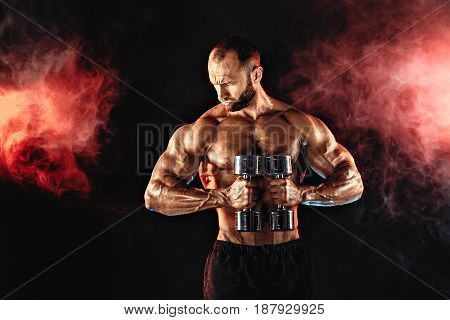 Portrait of muscular man lifting dumbbell in red smoke. Studio shot.