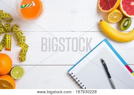 Fitness concept with fruit, bowl of oatmeal and centimeter. Top view background concept. Copy space. Pen and notepad for notes