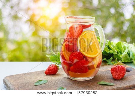 Strawberries oranges and mint for a refreshing drink on blurred background.