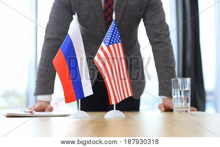 Russian flag and flag of European Union with businessman near by
