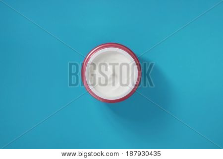 White cream for skin in a pink container on a blue background. View from above.