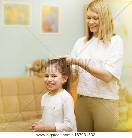 Mother Is Braiding Her Young Daughter's Hair Standing In The Children Room.