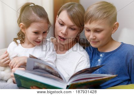 Beautiful Mother Is Reading A Book To Her Young Children. Sister And Brother Is Listening To A Story