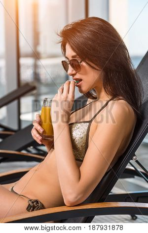 Young attractive slim girl in bikini relaxing on deck chair in wellness spa hotel resort. Woman holding a glass of orange juice
