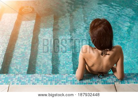 Beautiful woman relaxing at the luxury poolside. Girl at travel spa resort pool. Summer luxury vacation.