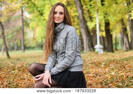 The girl squats in autumn wood in shining sun beams.