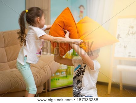 Happy family. Sister and brother are playing on the floor at home. Young boy and lovely girl having fun in children room.