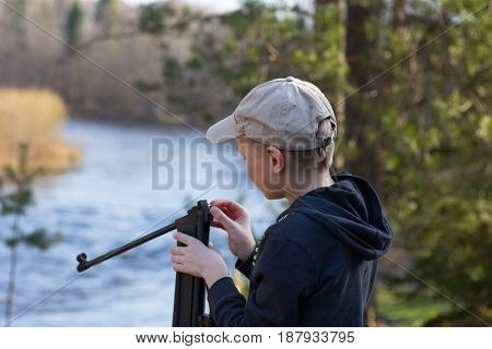teenager with air gun in forest near a river