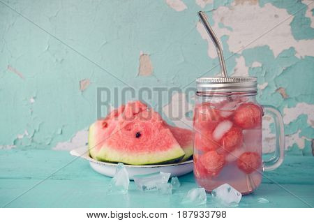 Watermelon drink in glass mason jar with slices of watermelon and ice on blue background with place for text. Summer fresh fruit flavored infused detox water. Copy space.