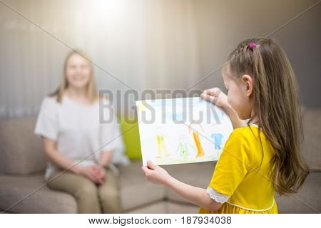 Child Daughter Congratulates Mom And Gives Her Painting. Mum And Girl Smiling And Hugging. Family Ho