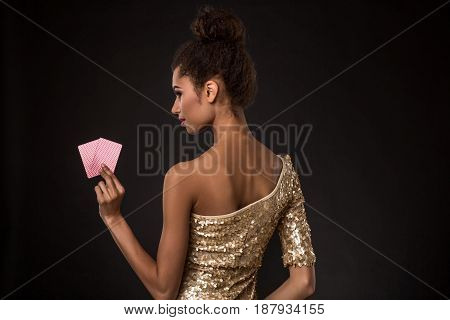 Woman winning - Young woman in a classy gold dress holding two cards, a poker of aces card combination. Studio shot on black background. A young woman stands with her back