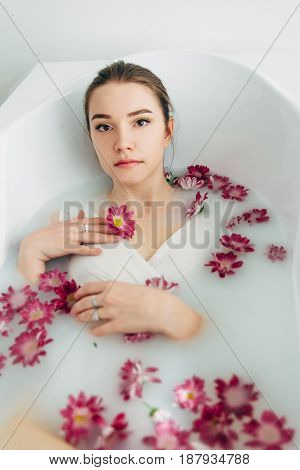 Woman Lies In A Bath With Milk Among The Flowers