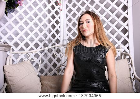 Attractive asian girl sitting on the couch and looking at the camera.