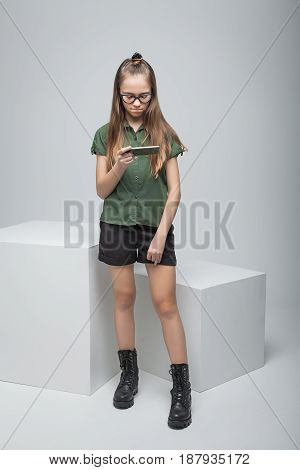 Young beautiful girl with phone near big white cube. woman dressed in green T-shirt, black shorts and large army boots
