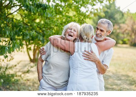 Senior friends having fun in the garden in summer laughing