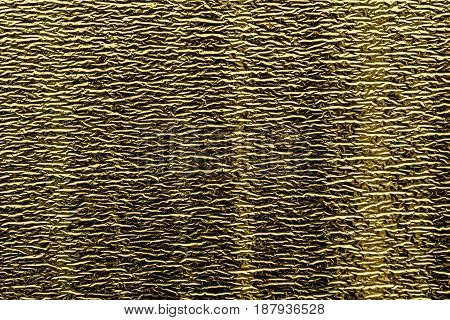 Background of goldy shiny foil with fine horizontal stamping