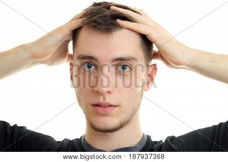 Portrait of a charming handsome guy who looks at the camera and holding up hands head isolated on white background close-up