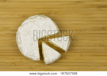 Brie Cheese And A Slice On A Wooden Board.