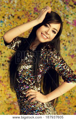 Young happy smiling woman wearing colorful shiny sheath dress with sequins, standing against yellow background. Party concept. Pretty slim brunette girl posing in sun light