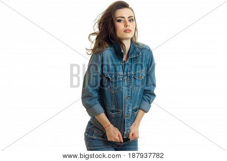 young beautiful girl in jeans suit stands up straight and looks isolated on white background