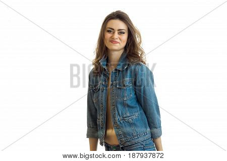 smiling beautiful brunette stands in jeans jacket and looks into a camera isolated on white background