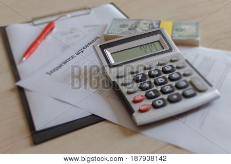 Car and Homeowner Insurance form with much dollars pen and calculator. Insurance concept