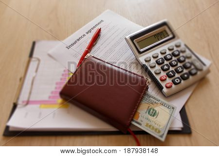 Insurance form with pen notebook dollars calculator on the table. Insurance concept