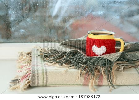 Cup of hot tasty drink and warm plaids on windowsill