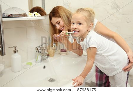 Little girl with her mother brushing teeth near sink in bathroom