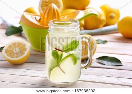 Delicious lemon juice in mason jar on wooden table