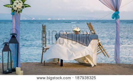 Cafe Table on a tropical sandy beach with sea on background, Nusa Dua, Bali.