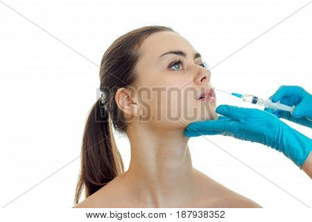 doctor in blue gloves work hard facial injection at the beautiful young woman close-up isolated on white background