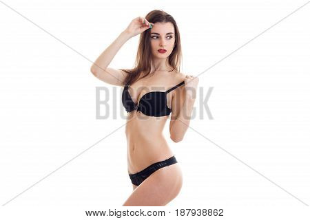 gorgeous sexy girl in black lingerie with a nice slender body posing sideways to the camera isolated on white background