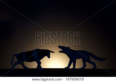 concept conflict.Bull versus wolf silhouette on a dark background
