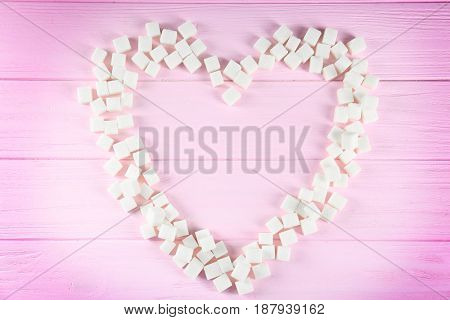 Sugar cubes in heart shape on wooden table