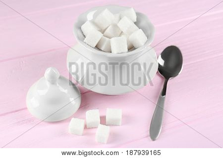 Sugar cubes with bowl and spoon on wooden table