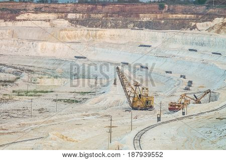Work of heavy grab excavators in the chalk quarry. Heavy mining industry. Clamshell excavators in the lowland quarry.