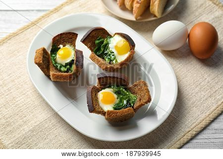 Plate with tasty eggs and spinach on wooden table