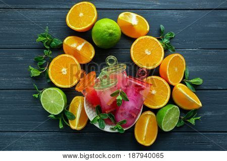 Bowl with delicious citrus popsicles and fresh fruits on wooden table