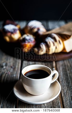 Croissant and white cup of black coffee on brown canvas. the croissant with coffee and notepad