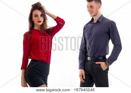 charming pretty girl in red keeps hand hair and stands next to guy isolated on white background