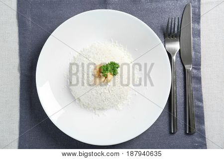 White plate with tasty coconut rice on table