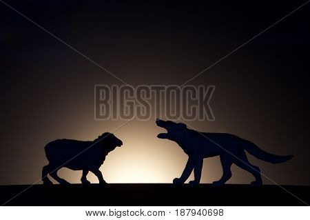 concept conflict.Sheep versus wolf silhouette on a dark background