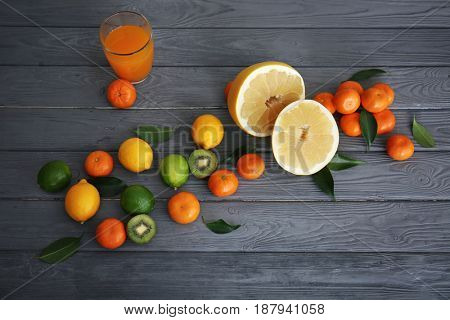 Glass of juice, halves of pomelo and fresh citrus fruits on wooden background