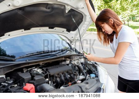 Stressed woman taking photo of engine with mobile phone - car breakdown