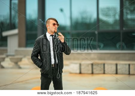 Portret Of A Handsome Young White Guy With Modern Haircut In Aviator Sunglasses And Headphones Smoki