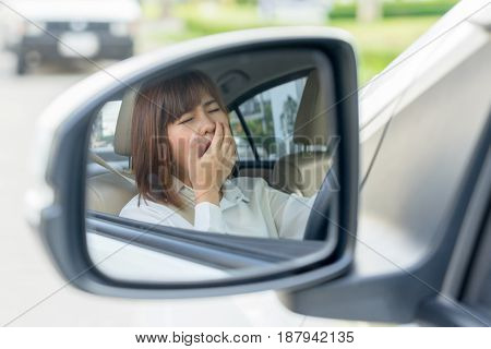 Closeup portrait sleepy tired young woman driving her car after long hour trip in mirror Sleep deprivation accident concept