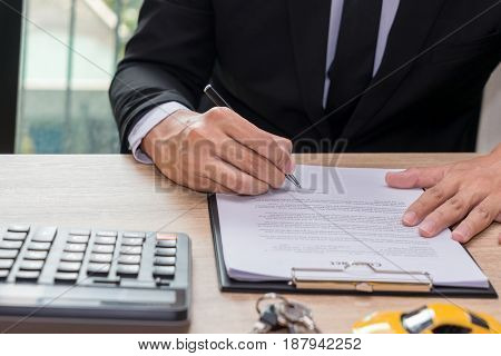 Businessman signing car loan agreement contract with car key and calculator on wooden desk