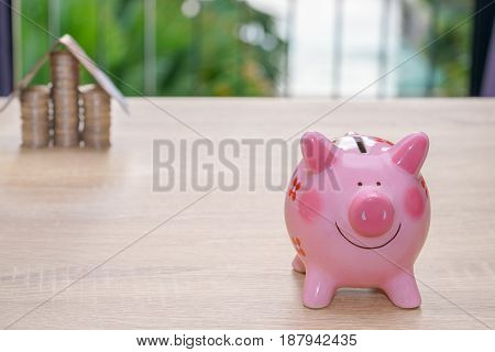 Pink piggy bank on wooden desk - save money to buy house concept