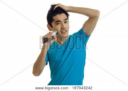 young charming guy in the blue shirt holds the hand of her hair looks ahead and shaves machine is isolated on white background